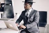 African confident businessman in suit , glasses and dandy hat working on laptop, analysing last reports from stocks exchange. - 246952607