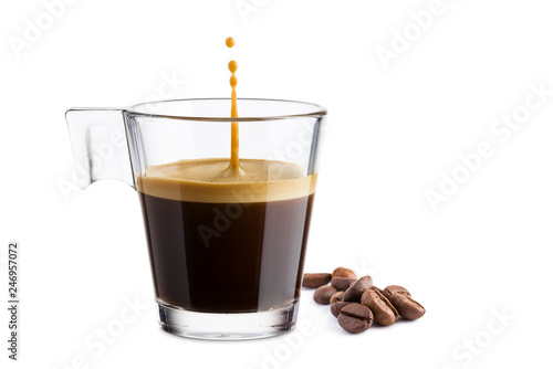 Black coffee in glass cup with coffee beans and  jumping drop on white background © winston