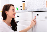Woman Pressing Button Of Dishwasher