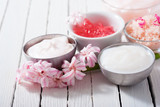 beauty and cosmetic creams with pink flowers on white wood
