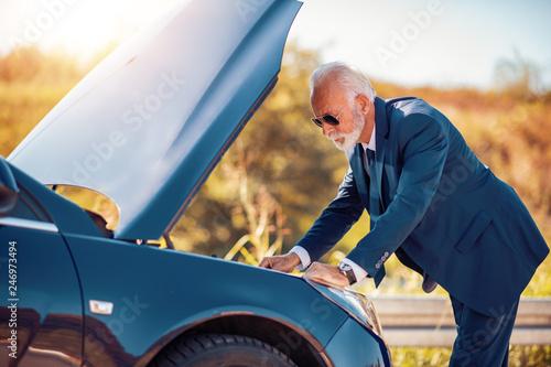 fototapeta na ścianę Senior businessman having problem with a car
