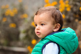 Outdoor portrait of mixed raced toddler in a garden, out of focus marigold flowers in the background. - 246976825