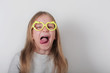 Portrait of funny naughty little girl in glasses making faces at camera, shows tongue. Expressive facial expressions . Human emotions, reactions, feelings and attitude .