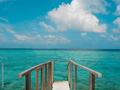 wooden pier extends into the sea on a amazing background of blue sea and sky. - 246985631