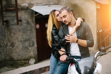 Couple on motorbike near old building
