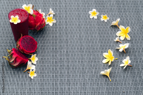 Glass of dragon fruit smoothie and fruits with plumeria flowers on a textured background