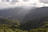 Anaga mountains northeast of Tenerife Canary Islands Spain. Sunlight penetrates through clouds into the valley. Viewed from Mirador Pico del Ingles. - 247003074