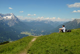 Young man enjoys idyllic mountain landscape with a village and mountains in the background - 247015288
