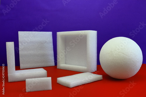 A color image of white styrofoam shapes on a red table with a purple background. - 247030635