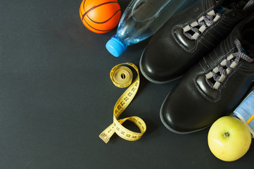 sneakers, tape measure, fruit and water in a bottle on black background with copy space, slimming concept, healthy life concept