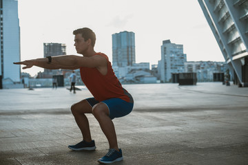Focused male athlete making physical exercise outdoor