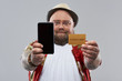 Cheerful bearded man showing gold card and smartphone