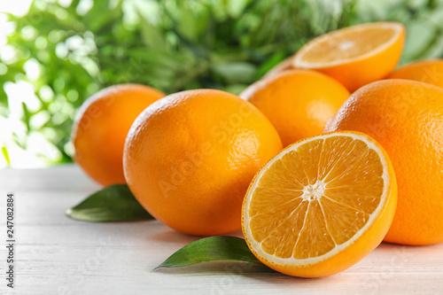 Leinwandbild Motiv Fresh juicy oranges with leaves on wooden table