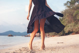 Young beautiful happy sensual woman in love in a stylish dress happily joyfully spinning on the beach, beauty and fashion, leisure and travel concept