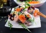 Vegetarian vietnamese spring rolls with spicy shrimps, prawns,  carrot, cucumber, red cabbage and rice noodle. Seafood. Tasty meal. Copy space