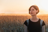 Backlit portrait of a woman in sunset. Female person standing in evening sunlight at a field - 247111204