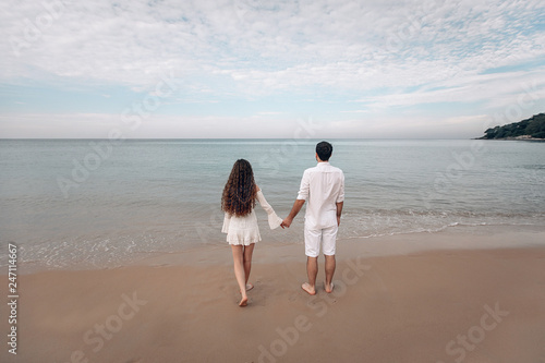 fototapeta na ścianę Young Couple looking at the sea and overcast sky in white clothing. Back view. Phuket. Thailand. Trip to warm destination.