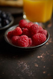 Close up on fresh raspberries placed on ceramic saucer on dark rusty table. Selective focus. Healthy breakfast ingredient.
