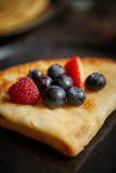 Close up on pancake with fresh fruit topping placed on dark rusty table. Selective focus. Healthy homemade breakfast concept.