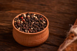 Peppercorns in a wooden bowl on table with food rustic style. Homemade food