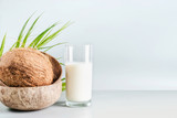 Coconut milk in glass on table with whole coconut, front view, banner. Healthy detox nutrition, vegan food and clean eating concept. Copy space, banner