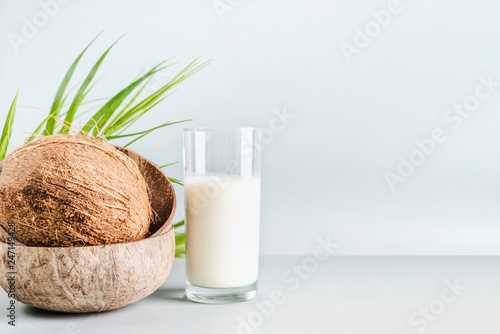 Leinwandbild Motiv Coconut milk in glass on table with whole coconut, front view, banner. Healthy detox nutrition, vegan food and clean eating concept. Copy space, banner