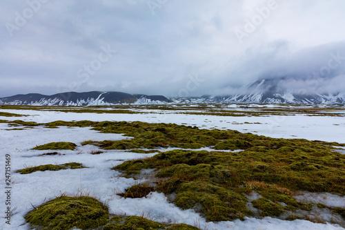 Isländische Winterlandschaft mit Bergen, See und Moos