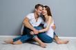 Leinwanddruck Bild - Beautiful young amorous couple, sitting on floor