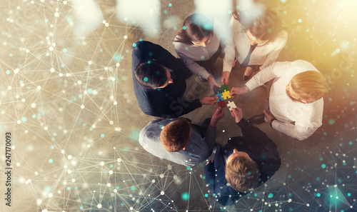 Business people join puzzle pieces in office. Concept of teamwork and partnership. double exposure with internet network effects - 247170093