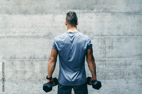 Leinwanddruck Bild Dedicated bodybuilder in sportswear standing in front of the wall and holding dumbbells in hands, backs turned.