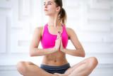 Young attractive woman practicing yoga, sitting in Padmasana, exercise, Lotus pose, namaste.