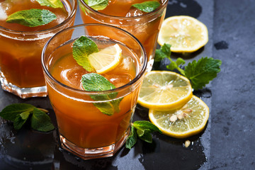 refreshing iced tea with mint and lemon on dark background, closeup