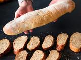 Fresh bakery. Business startup. Hands holding baguette over wholegrain bread slices.