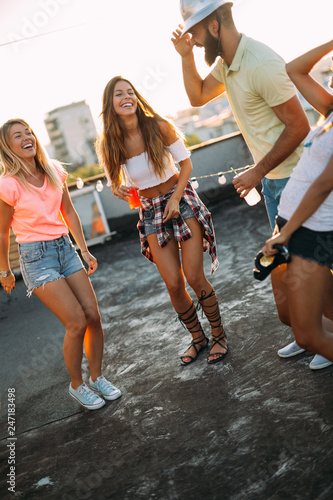 Foto Murales Group of happy friends having party on rooftop