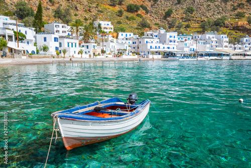 Leinwandbild Motiv Fishing boat and the scenic village of Loutro in Crete, Greece