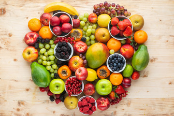 Heart made from healthy rainbow fruits, strawberries raspberries oranges plums apples kiwis grapes blueberries mango persimmon pineapple on light wooden table, top view, copy space, selective focus © Liliya Trott
