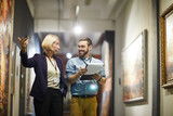 Portrait of two cheerful museum workers discussing paintings walking in art gallery, copy space - 247185860