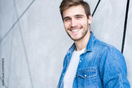 Leinwandbild Motiv Perfect man. Portrait of happy fashionable handsome man in jeans shirt.
