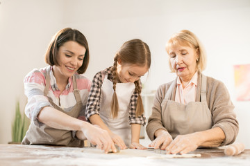 Little girl and two women in aprons using cookie cutters while making homemade pastry