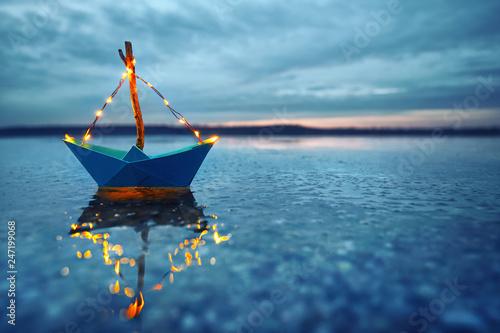 Leinwanddruck Bild romantischer Abend - leuchtendes Boot am Strand