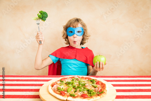 Leinwanddruck Bild Superhero child eating superfood