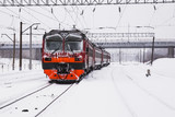 passenger train is slowly traveling on a snowy railway