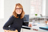 Confident businesswoman wearing casual clothes while sitting at office and working - 247217249