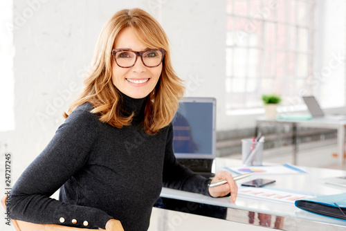 Leinwandbild Motiv Confident businesswoman wearing casual clothes while sitting at office and working