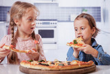 Little cute child girl best friends eating a pizza piece. Food, happy childhood concept.