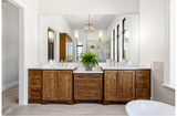 Beautiful bathroom in new luxury home, with double vanity, bathtub, and shower visible in mirror reflection. - 247219413