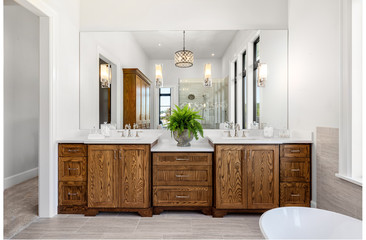 Beautiful bathroom in new luxury home, with double vanity, bathtub, and shower visible in mirror reflection.
