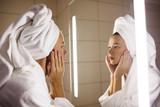 Woman looking on her mirror in bathroom - 247220459