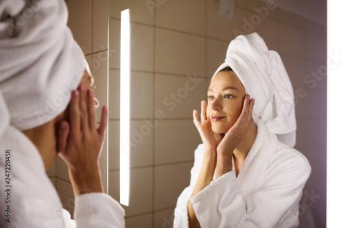 Leinwandbild Motiv Woman looking on her mirror in bathroom