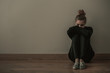 Young woman with anxiety disorder wearing dark clothes sitting on the floor, copy space on empty wall - 247230451